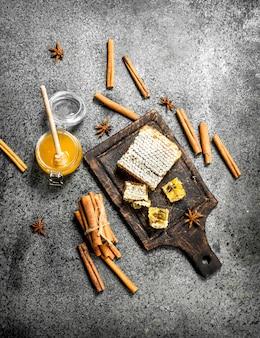 Verse honing met pijpjes kaneel. op rustieke achtergrond.