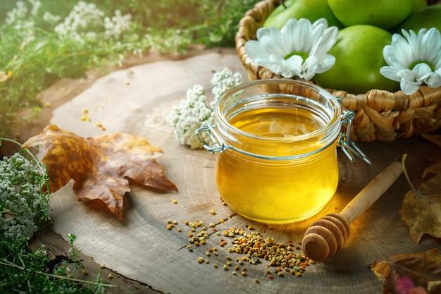 Verse honing, stuifmeel en rijpe appels op een houten tafel