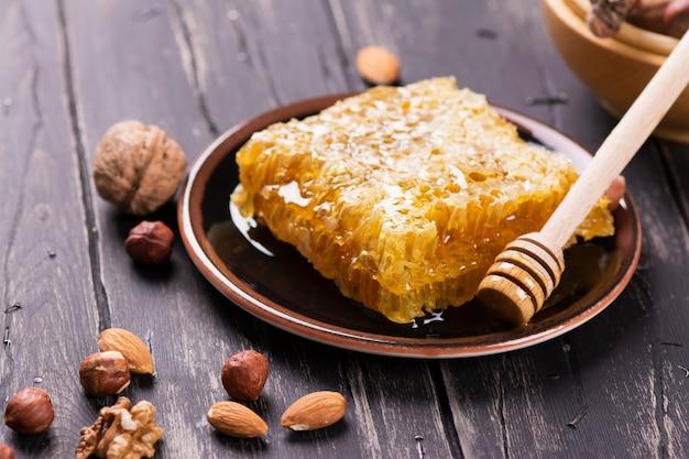 Verse honingraat en assortiment van noten op zwarte houten achtergrond.