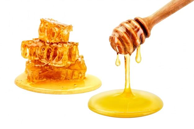 Verse honingraat met honing op wit.