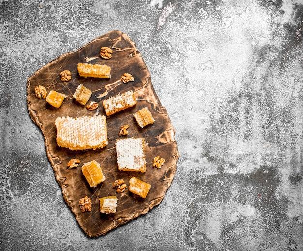 Verse honingraat met noten. op rustieke tafel.