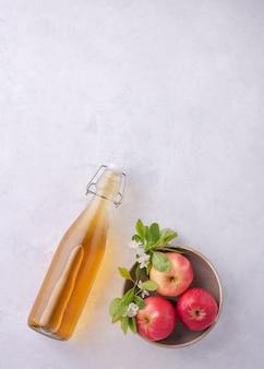 Verse huisgemaakte appelcider met appel op grijze achtergrond