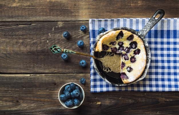 Verse huisgemaakte nederlandse baby pannenkoek met bosbessen in ijzeren koekepan bestrooid met poedersuiker op rustieke houten tafel. bovenaanzicht.