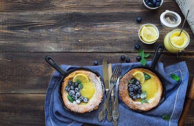Verse huisgemaakte nederlandse baby pannenkoek met lemon curd en bosbessen in ijzeren koekenpannen op rustieke houten ondergrond. bovenaanzicht. kopieer de ruimte.