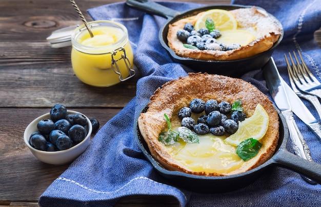 Verse huisgemaakte nederlandse baby pannenkoek met lemon curd en bosbessen in ijzeren koekenpannen op rustieke houten.