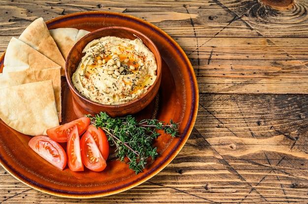 Verse hummus met pitabroodje, tomaat en peterselie op een rustieke plaat. houten achtergrond. bovenaanzicht. ruimte kopiëren.