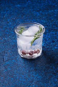 Verse ijskoude koolzuurhoudende waterdrank in glas op blauwe gestructureerde achtergrond, hoekmening