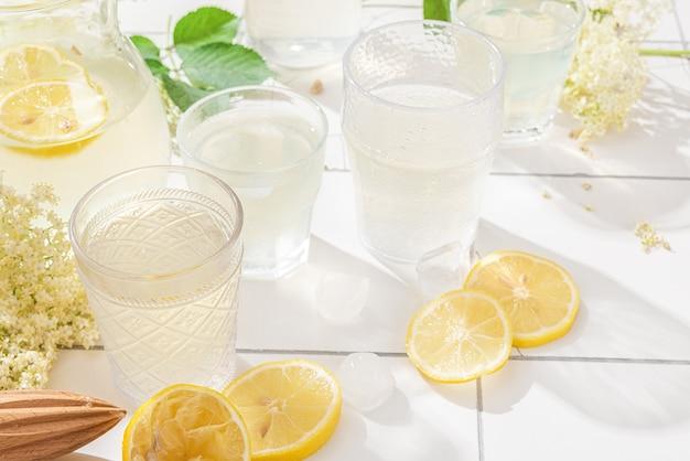 Verse ijslimonade met citroenen en vlierbessenbloemen in een pot en glazen op witte tegeltafel met harde schaduwen Premium Foto