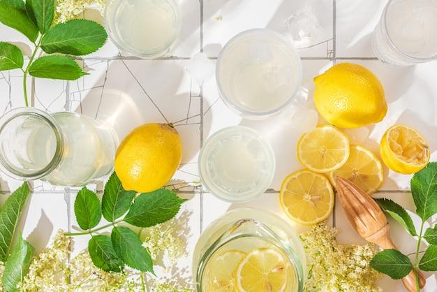 Verse ijslimonade met citroenen en vlierbessenbloemen in flessen en glazen op witte tegeltafel met schaduwen