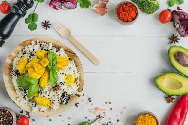 Verse ingrediënten en gebakken rijst in houten plaat met vork boven tafel
