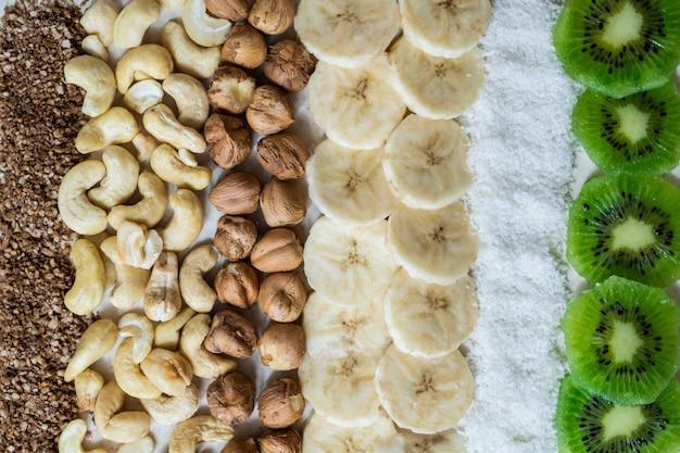Verse ingrediënten voor een gezond rauw voedselontbijt. kiwi, kokosschilfers, cashewnoten en hazelnoten van bovenaf geschoten, ingrediënten voor een smoothiekom