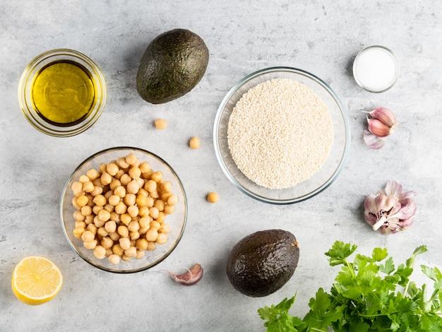Verse ingrediënten voor gezonde voeding hummus, cheak erwten, avocado, olijfolie, teentjes knoflook, sesam, zout, citroen en groene peterselie. bovenaanzicht, platte lay-out, wit grijs