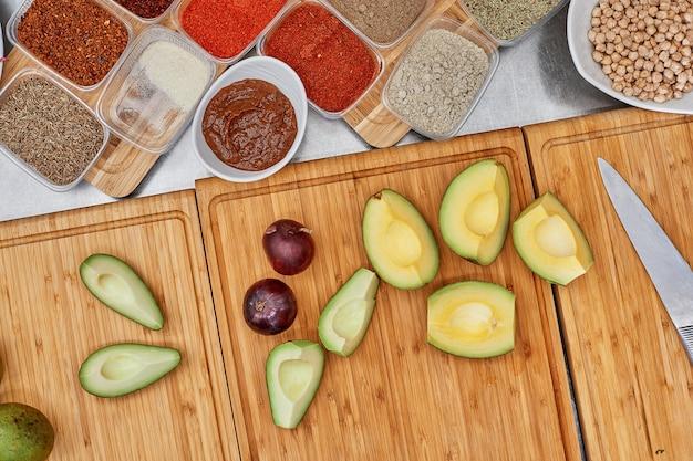 Verse ingrediënten voor het maken van salades of dipsauzen: avocado, tomaten, noten, olie op rustieke ondergrond, bovenaanzicht, plaats voor tekst