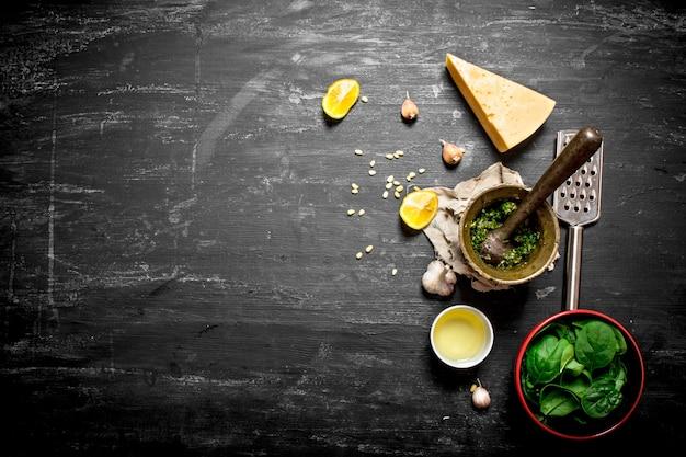 Verse ingrediënten voor italiaanse pesto. op de zwarte houten tafel.