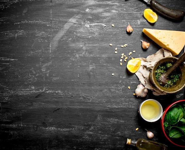Verse ingrediënten voor italiaanse pesto op de zwarte houten tafel.