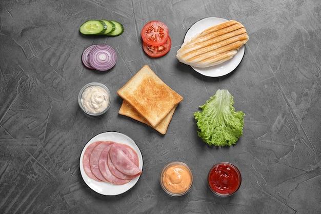 Verse ingrediënten voor smakelijke sandwich op grijze achtergrond, plat gelegd