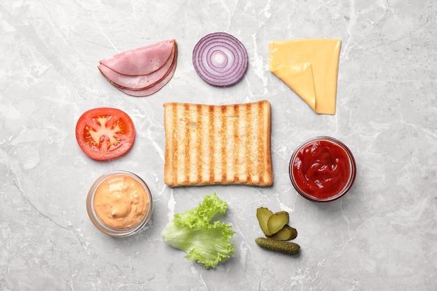 Verse ingrediënten voor smakelijke sandwich op lichtgrijze ondergrond, plat gelegd