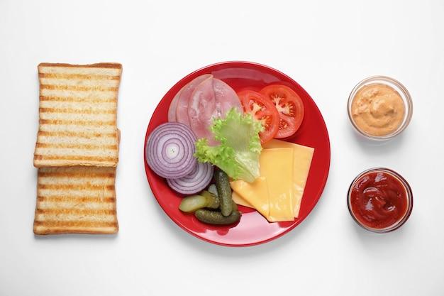 Verse ingrediënten voor smakelijke sandwich op witte achtergrond, bovenaanzicht