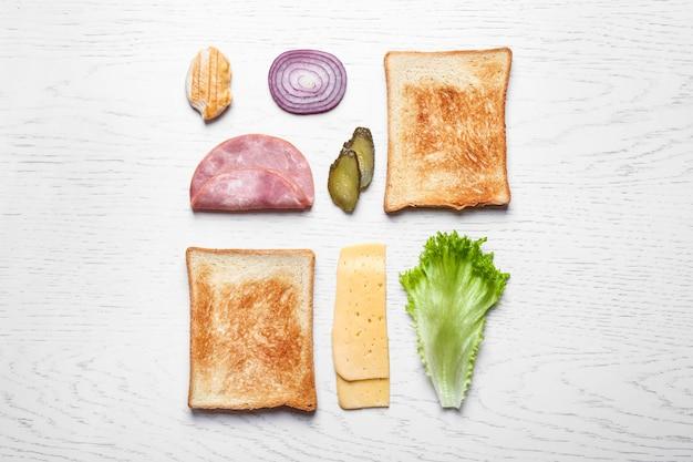 Verse ingrediënten voor smakelijke sandwich op witte houten ondergrond, plat gelegd