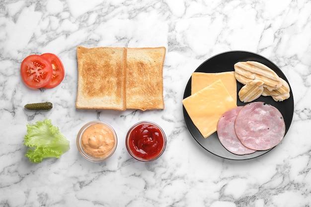 Verse ingrediënten voor smakelijke sandwich op witte marmeren achtergrond, plat gelegd
