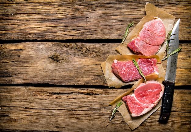 Verse inzet van rauw vlees en kruiden en hakmes. op houten tafel. vrije ruimte voor tekst. bovenaanzicht