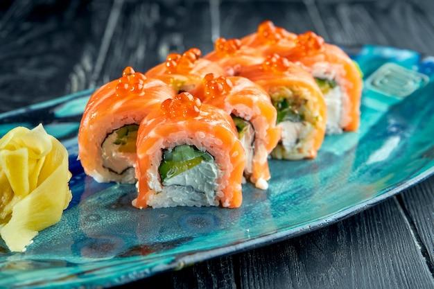 Verse, japanse sushirolletjes met komkommer, kaviaar en zalm, geserveerd in een bord met wasabi en gember op een donkere ondergrond. japanse keuken. rode drakenrol in sesam