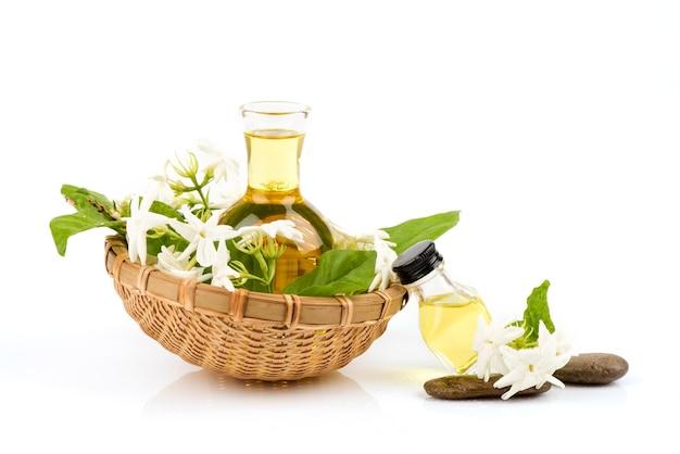 Verse jasmijnbloemen en etherische olie die op wit wordt geïsoleerd.