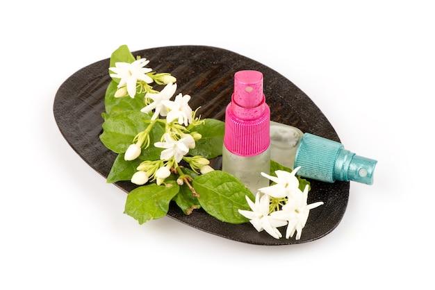 Verse jasmijnbloemen en gewonnen in de spray op wit wordt geïsoleerd.