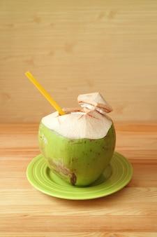 Verse jonge kokosnoot met geel stro op een groene plaat klaar om te drinken