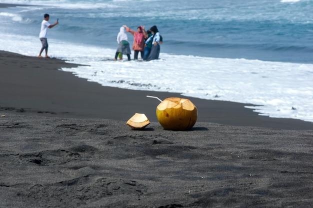 Verse jonge kokosvruchten op het donkere zandstrand in pantai dewa ruci purworejo, indonesië, geselecteerde focus met wazig van mensen die foto's nemen op de achtergrond