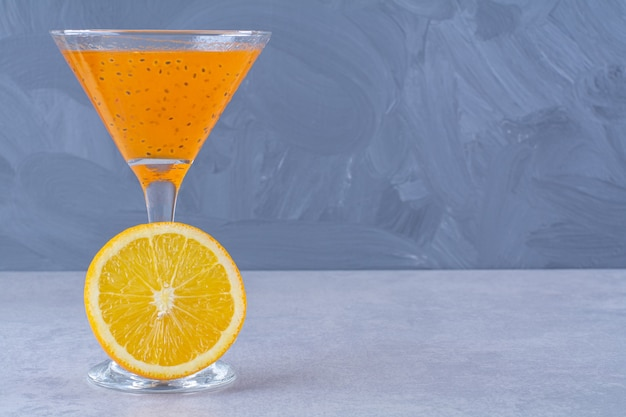 Verse jus d'orange naast schijfje sinaasappel op het marmer.