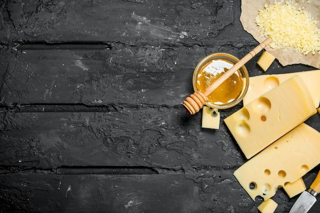 Verse kaas en honing. op zwarte rustieke achtergrond.