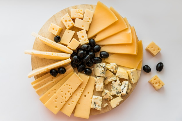 Verse kaas en olijven op houten hakbord