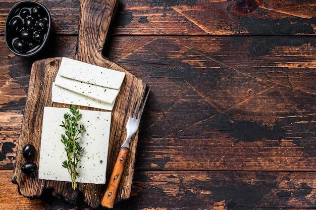 Verse kaas feta met tijm en olijven. donkere houten achtergrond. bovenaanzicht. ruimte kopiëren.