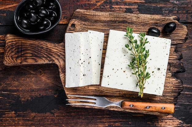 Verse kaas feta met tijm en olijven. donkere houten achtergrond. bovenaanzicht.