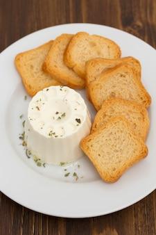 Verse kaas met toast op witte plaat