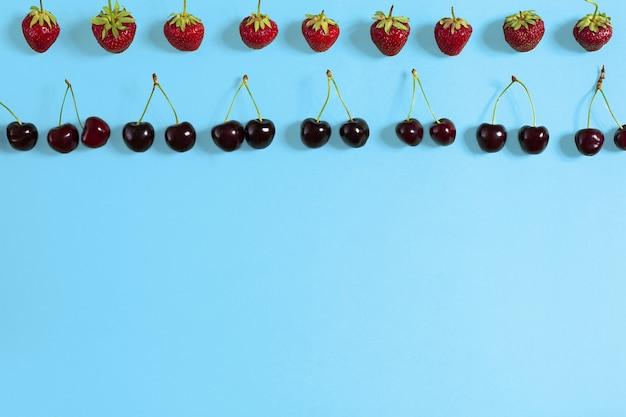 Verse kersen en aardbeien op blauwe achtergrond bovenaanzicht