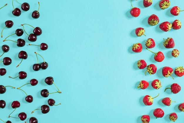 Verse kersen en aardbeien op mint achtergrond bovenaanzicht