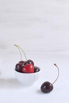 Verse kersen in witte porseleinen kom gewichtsverlies gezond eten zomerfruit en bessen oogsten biologisch fruit