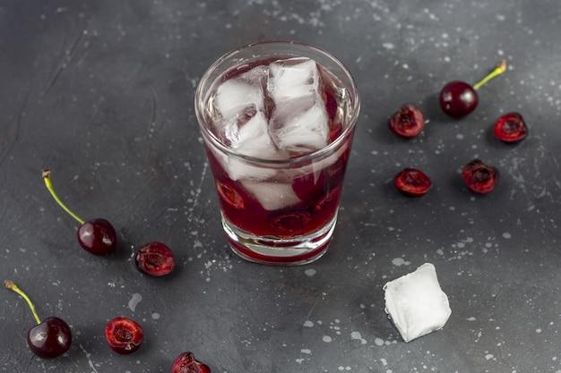 Verse kersencocktail. een cocktail met gin of wodka, kersensiroop en stukjes kers en ijs