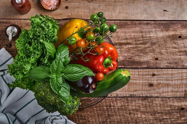 Verse kersentomatentakken, basilicumbladeren, servet, peper en pepermolen op oude houten rustieke achtergrond. eten koken achtergrond en mock up.