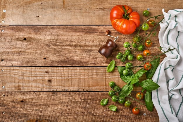 Verse kersentomatentakken, basilicumbladeren, servet, peper en pepermolen op oude houten rustieke achtergrond. voedsel koken achtergrond en mock up.