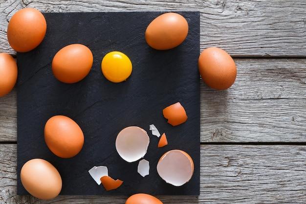 Verse kippeneieren bruin huis, gebarsten eierschaal en dooier op rustieke leisteen zwarte plaat op houten tafel. natuurlijk gezond voedsel en biologische kookingrediënten