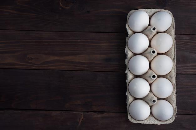 Verse kippeneieren in een pakket, rauwe eieren in een witte schaal in een doos.