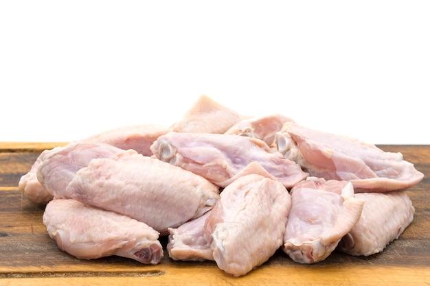 Verse kippenvleugels op een houten bord geïsoleerd op een witte achtergrond