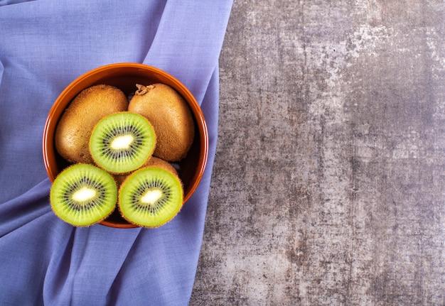 Verse kiwi bovenaanzicht in keramische kom op blauwe doek op het oppervlak