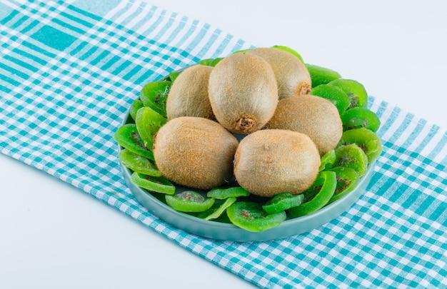 Verse kiwi in een plaat met gedroogde kiwi hoge hoekmening over wit en picknick doek achtergrond