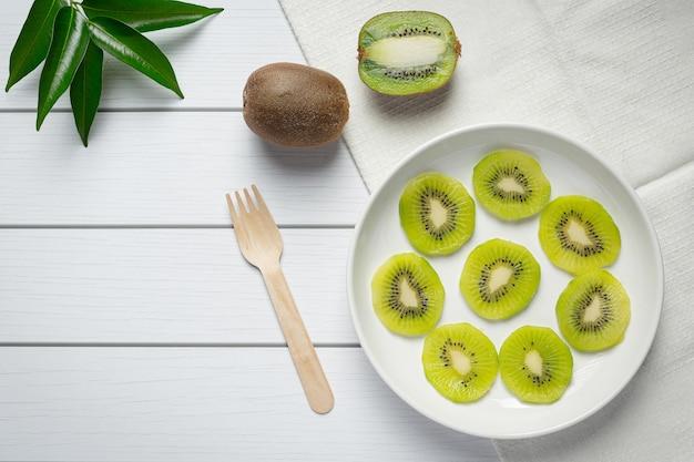 Verse kiwi, in stukjes glijden, op een witte plaat leggen