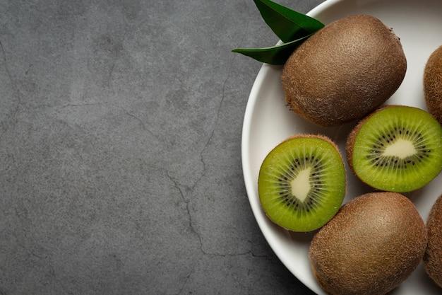 Verse kiwi, in tweeën gesneden, op een witte plaat gelegd