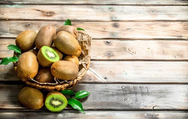 Verse kiwi met bladeren in de mand. op houten achtergrond